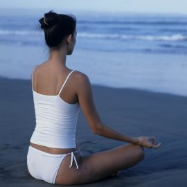 Lifestyle. Brunette Model Meditating on the Beach. JPEG